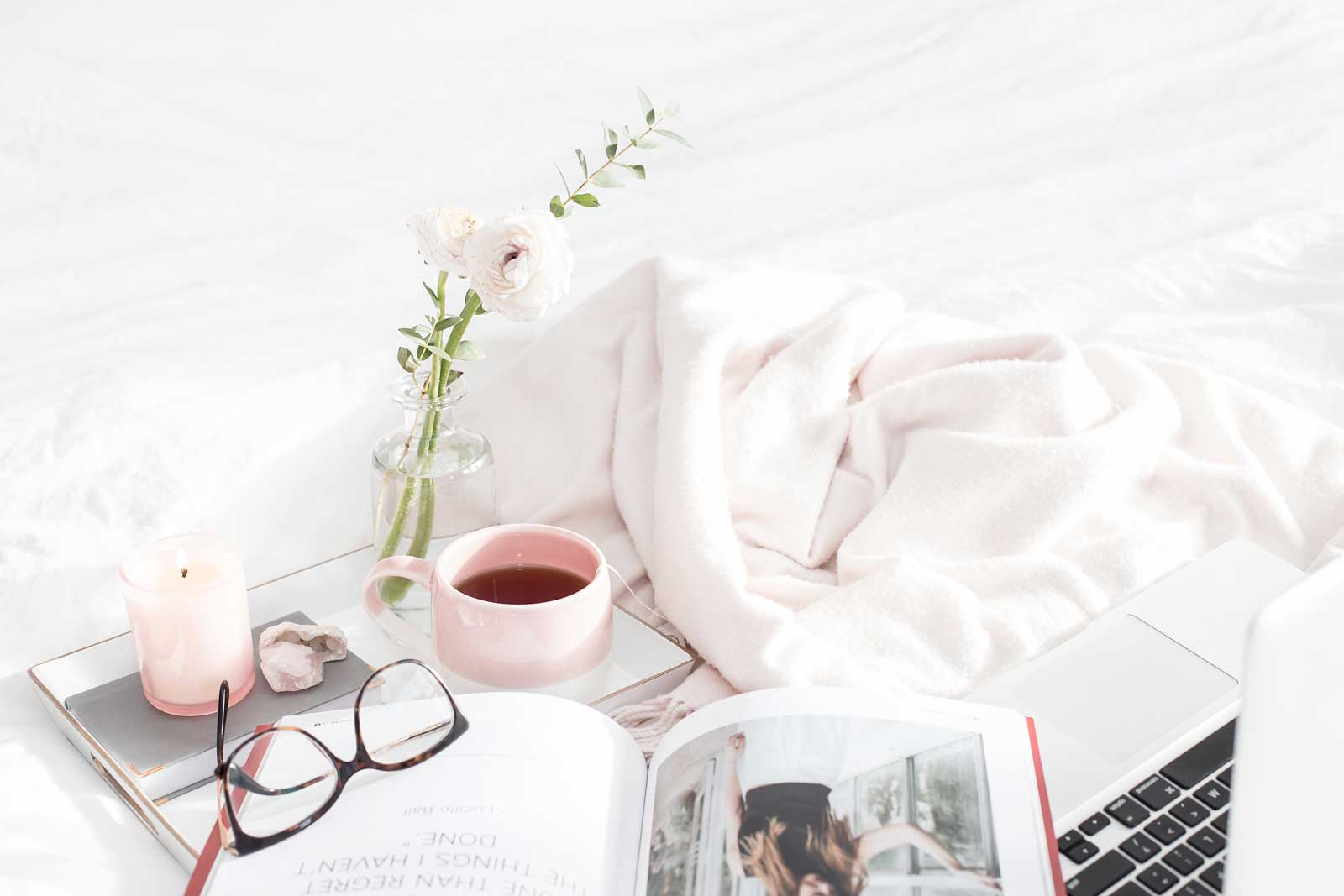 Open magazine, glasses and cup of coffee on bed